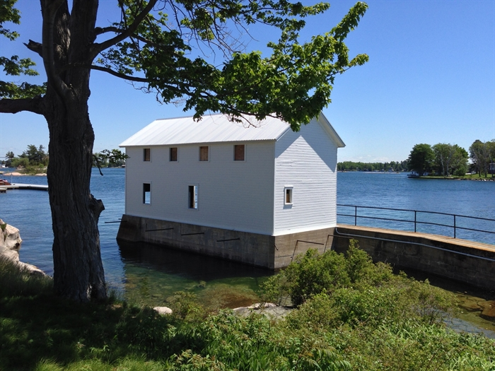 The boathouse has a fresh coat of paint on sides visible from the island.