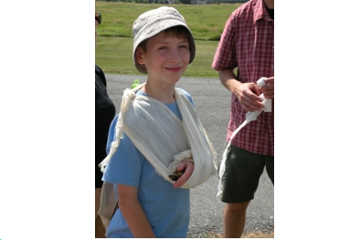 A happy camper demonstrates a rustic sling in Nature First-Aid